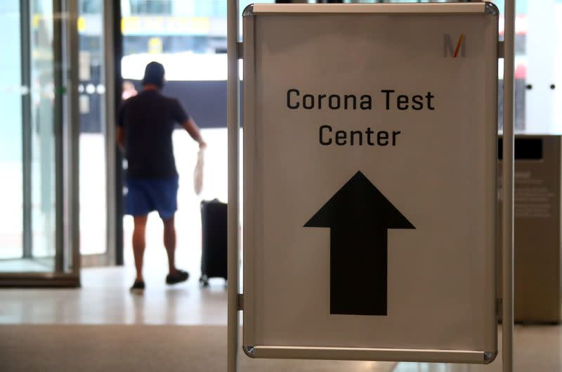 A passenger passes a sign leading to a test center for the coronavirus disease (COVID-19), at Munich International Airport