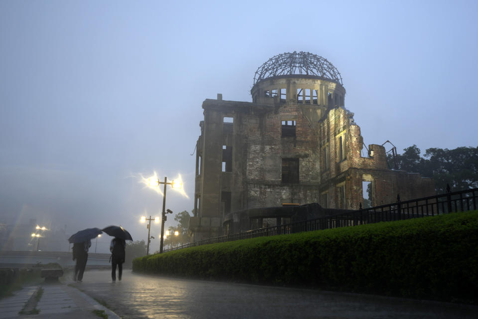 People hold umbrellas as they walk in a heavy rain near the Atomic Bomb Dome in Hiroshima, western Japan Thursday, July 15, 2021. Aug. 6, 2021, marks the 76th anniversary of the WWII U.S. atomic bombing. (AP Photo/Eugene Hoshiko)