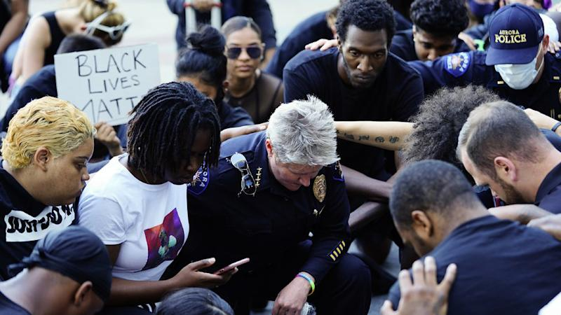 Protesters and police kneel together for eight minutes and 46 seconds during a peaceful protest against police brutality