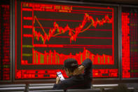 A Chinese investor uses his smartphone as he monitors stock prices at a brokerage house in Beijing, Tuesday, Nov. 19, 2019. Asian shares were mixed Tuesday as investor sentiment remained cautious amid worries about the next development in trade talks between the United States and China. (AP Photo/Mark Schiefelbein)