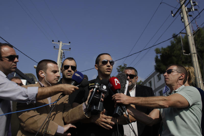 Ilias Kasidiaris, center, lawmaker of the extreme right party Golden Dawn speaks to reporters in front of the party's office in northern Athens, Saturday, Nov. 2, 2013. Police looking for clues to the Friday evening murder of two members of the far-right Golden Dawn party and the grievous injury to a third say the gun used in the attack has not been used in previous terrorist attacks. (AP Photo/Kostas Tsironis)