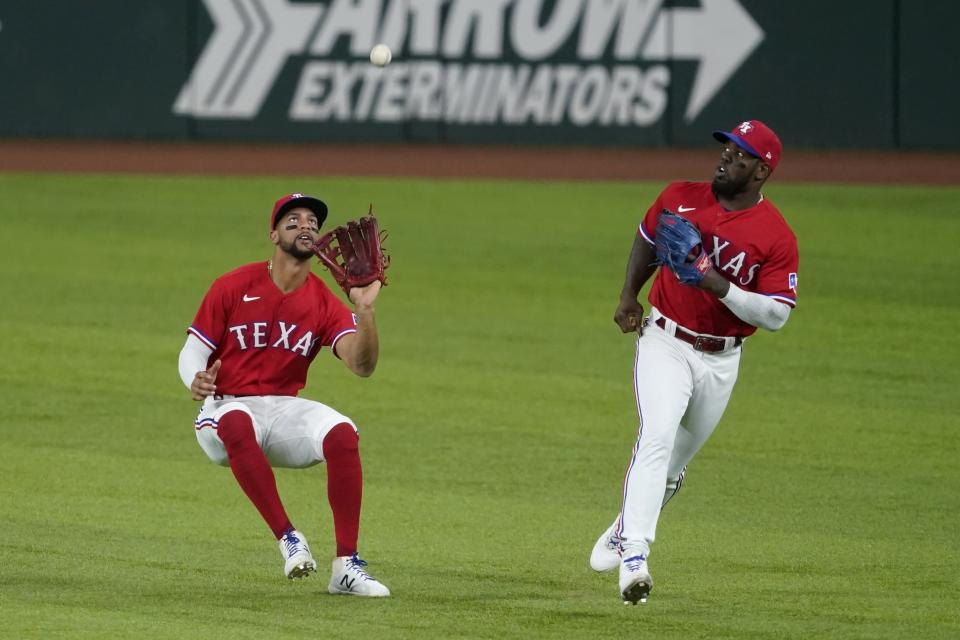 Texas Rangers center fielder Leody Taveras, left, waits to catch a fly ball hit by Chicago White Sox's Billy Hamilton as right fielder Adolis Garcia watches during the fifth inning of a baseball game in Arlington, Texas, Friday, Sept. 17, 2021. (AP Photo/Tony Gutierrez)
