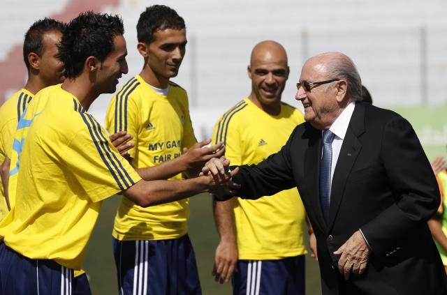 FIFA President Sepp Blatter (R) shakes hands with Palestinian coaches as he visits a football academy named after him, near the West Bank city of Ramallah May 27, 2014. REUTERS/Mohamad Torokman (WEST BANK - Tags: POLITICS SPORT)