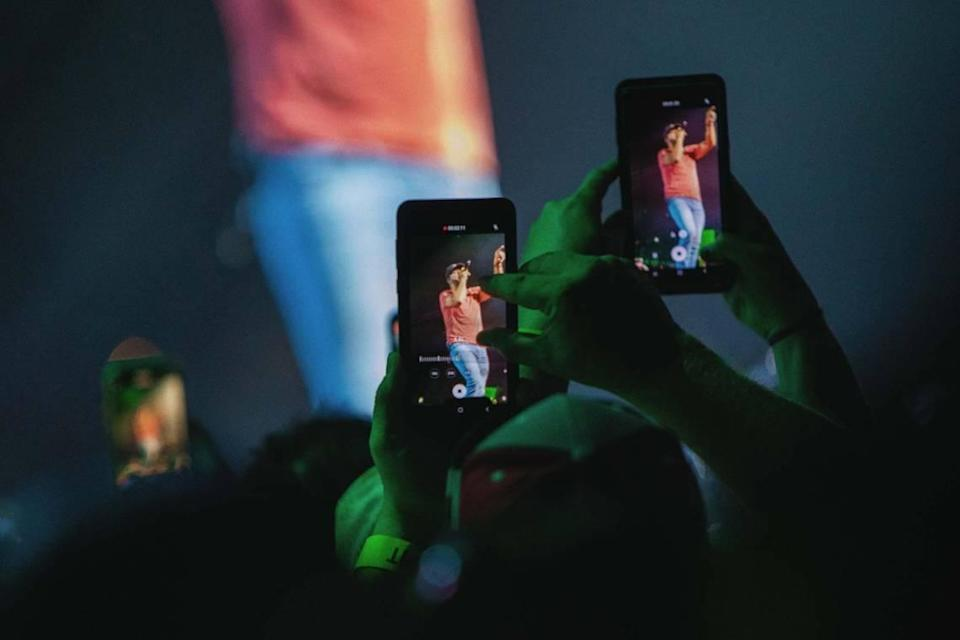 Fans capture moments from Friday night's concert on their cellphones.