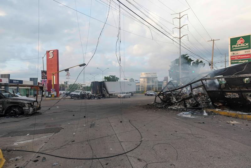 Burnt vehicles used by gunmen smolder on an intersection, one day after street battles with security forces, in Culiacan on Oct. 18. | Augusto Zurita—AP