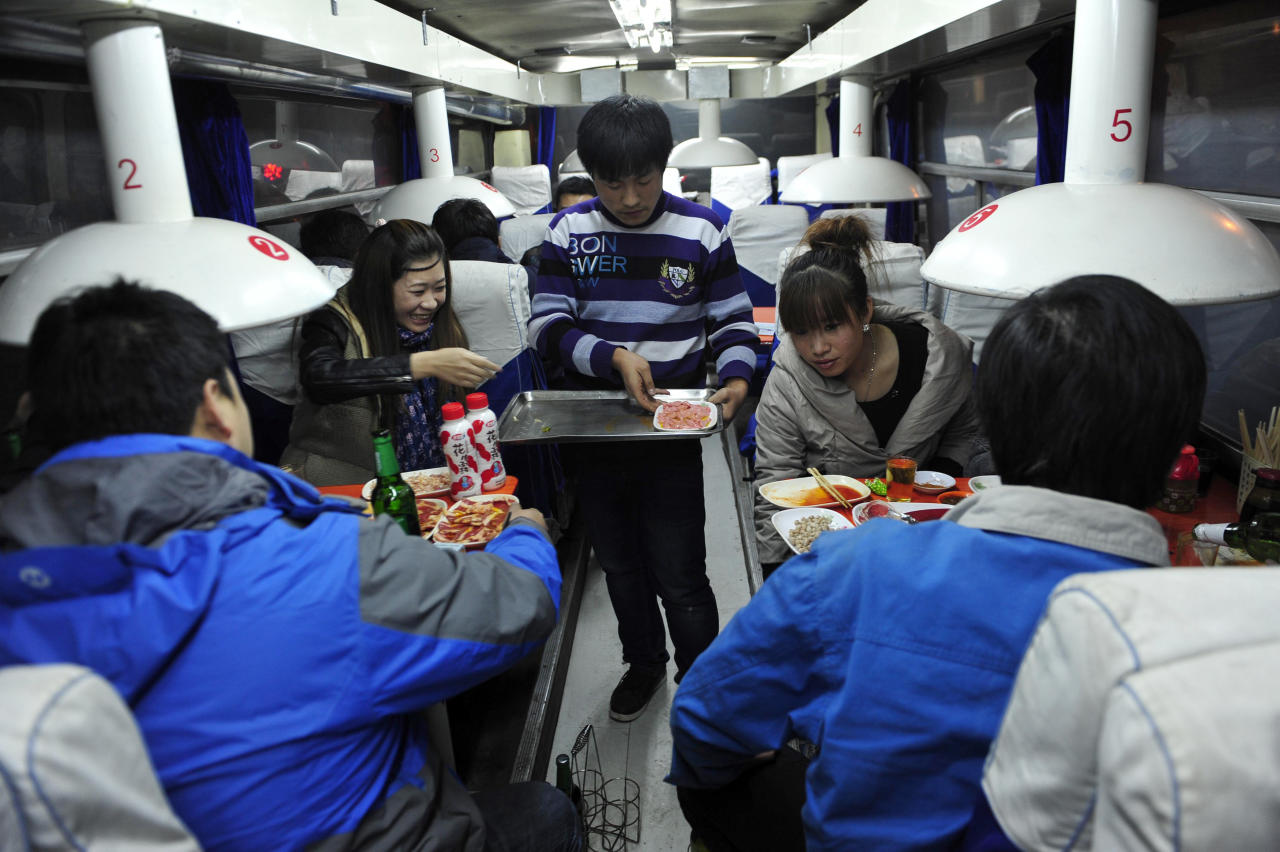 A waiter serves customers inside a coach restaurant in Shenyang, Liaoning province, November 8, 2012. A couple bought an old coach with around 20,000 RMB ($3,206) and transformed it into a barbecue restaurant a month ago in an old residential compound. Picture taken November 8, 2012. REUTERS/Stringer (CHINA - Tags: SOCIETY FOOD BUSINESS TRANSPORT)
