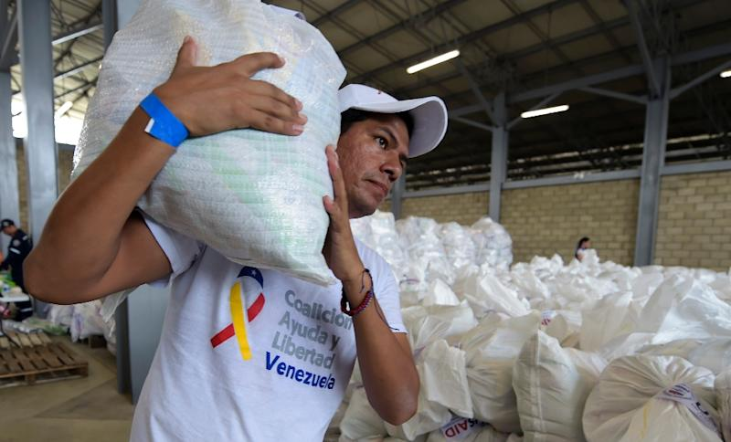 What happens to the sea of shiny white plastic bags filled with vital supplies now hinges on the military (AFP Photo/Raul Arboleda)