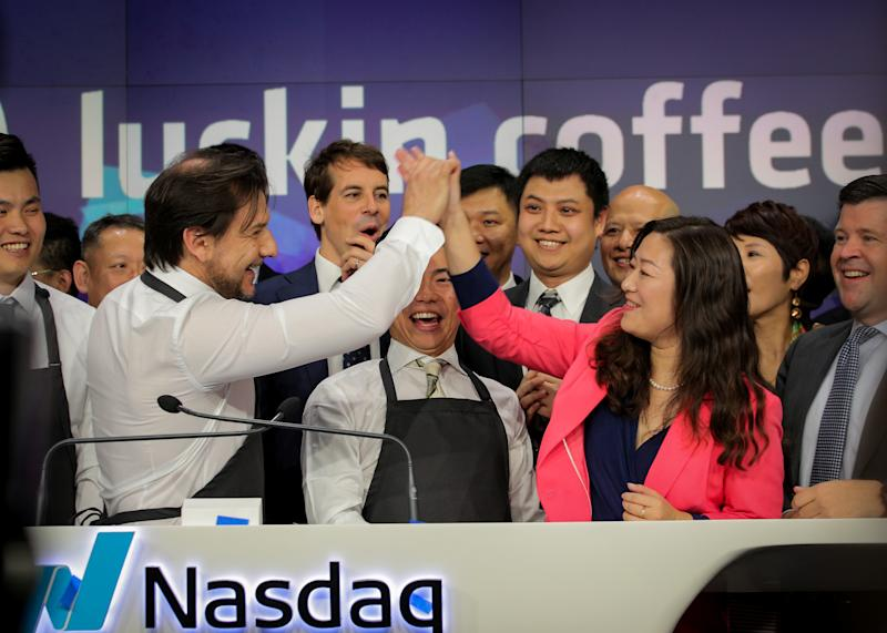 Jenny Qian Zhiya CEO of Luckin Coffee, exchanges high-five with an barista Andrea Lattuada during the company's IPO at the Nasdaq Market site in New York, U.S., May 17, 2019. REUTERS/Brendan McDermid