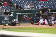 Atlanta Braves' Marcell Ozuna, left, slides safely into home as Washington Nationals' catcher Yan Gomes (10) tries a tag during the fourth inning of a baseball game against in Washington, Thursday, May 6, 2021. (AP Photo/Manuel Balce Ceneta)