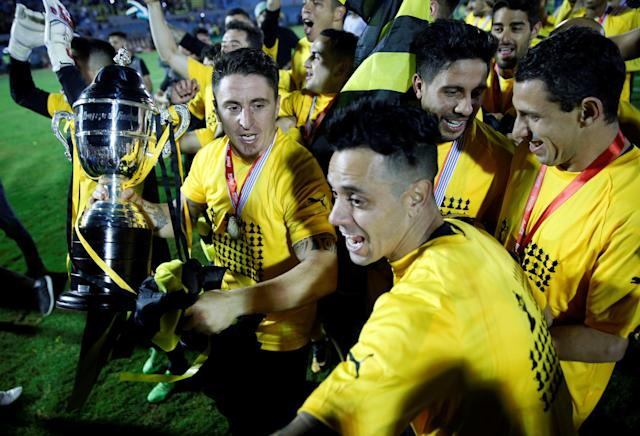 Soccer Football - Uruguayan Championship - Defensor Sporting v Penarol - Centenario stadium, Montevideo, Uruguay - December 10, 2017. Players of Penarol celebrate with the trophy of the Uruguayan championship after defeating Defensor Sporting in a penalty shoot-out. REUTERS/Andres Stapff