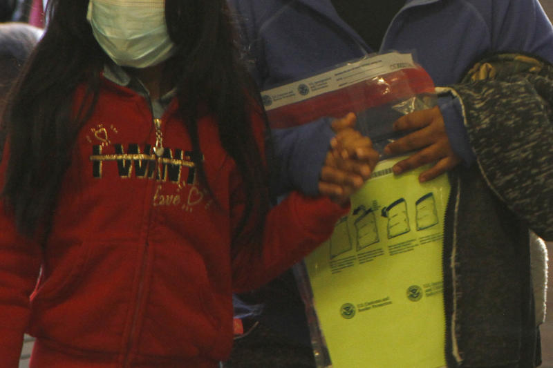 A woman carries a property bag issued by Customs and Border Protection while holding the hand of a girl wearing a mask as they arrive at a mandatory immigration court hearing on Monday, March 16, 2020, in El Paso, Texas. The migrants, who must wait in Ciudad Juarez, Mexico, wore masks following the first reported cases of COVID-19 in El Paso. The migrants are not suspected to be carrying the virus. (AP Photo/Cedar Attanasio)