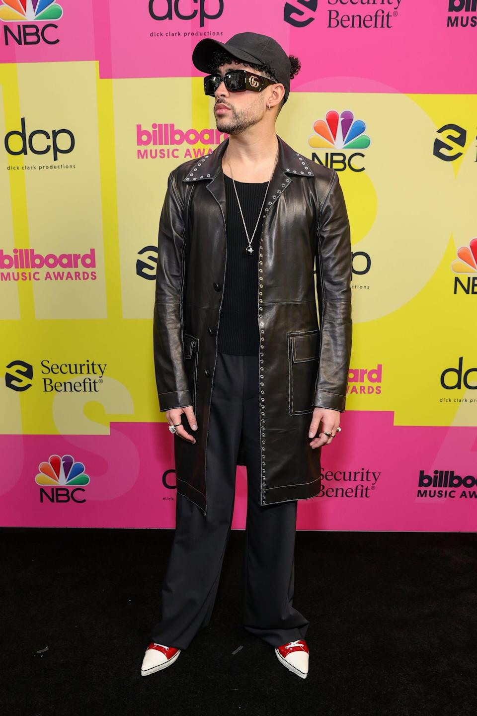<p>Wearing a leather trench with black trousers and Gucci sunglasses.</p>