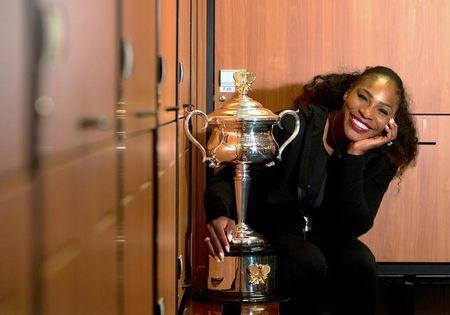 Serena Williams of the U.S. sits next to the trophy after winning the Women's singles final against sister Venus at the Australian Open tennis tournament in Melbourne, Australia in this handout image taken January 28, 2017. Fiona Hamilton/Courtesy of Tennis Australia/Handout via REUTERS