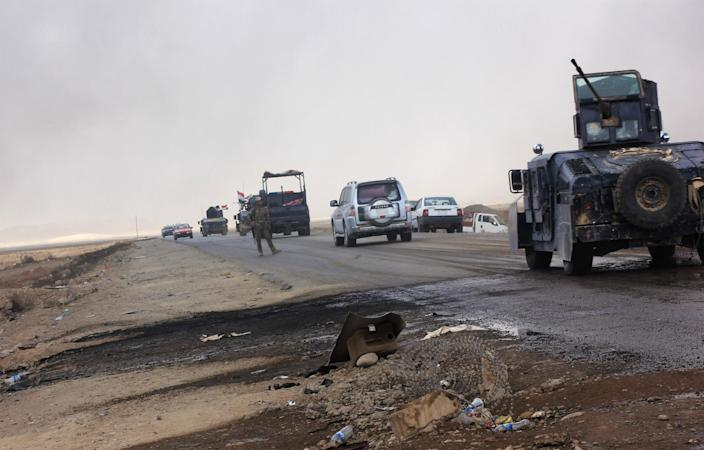 An Iraq military convoy heads north toward the crossing at the Qayyarah North checkpoint. (Photo: Ash Gallagher for Yahoo News)