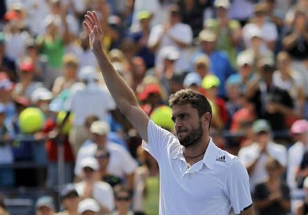 Gilles Simon of France waves after his win over David Ferrer of Spain during their match at the 2014 U.S. Open tennis tournament in New York, August 31, 2014. REUTERS/Eduardo Munoz