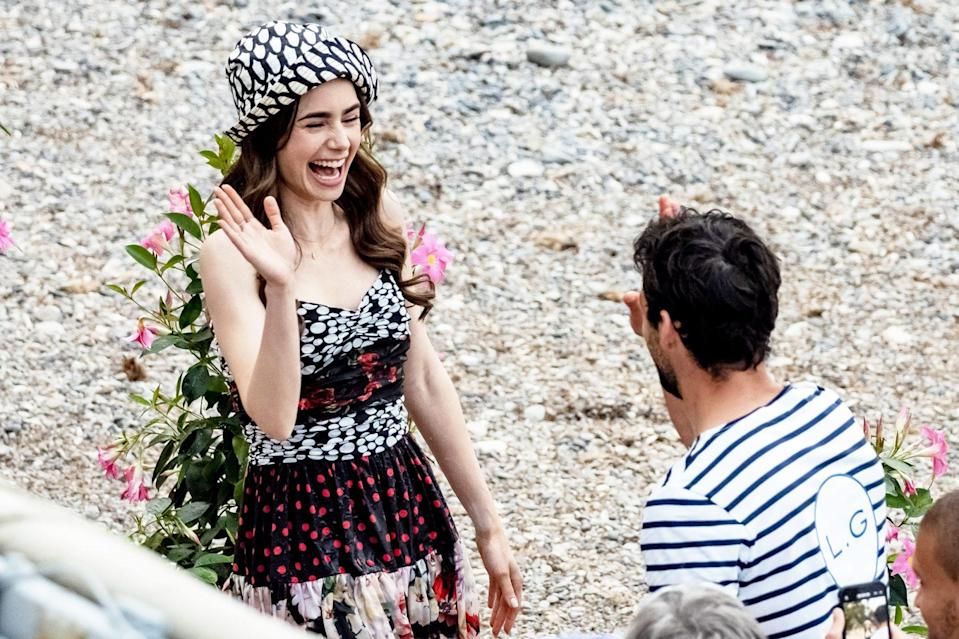 <p>Lily Collins gives her costar a high five while filming <em>Emily in Paris </em>in Saint-Jean-Cap-Ferrat, France on Tuesday. </p>