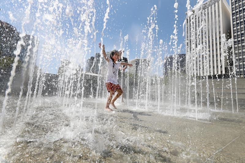 Charlee, 4, plays with her dad Vaughn Hampton in the Victoria Square fountain in Adelaide.