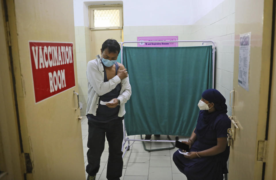 A man comes out after receiving COVID- 19 vaccine at a government hospital, in New Delhi, India, Monday, March 22, 2021. India has reported its highest number of coronavirus cases in four months, amid a worrying surge that has prompted multiple states to return to some form of restrictions on public gathering. (AP Photo/Manish Swarup)