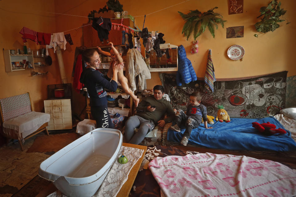 Karmen Bastyur, a 22 year old Hungarian Roma woman, lifts her daughter Fruzsina after giving her a bath in the family home which lacks running water in Bodvaszilas, Hungary, Monday, April 12,2021. Many students from Hungary's Roma minority do not have access to computers or the internet and are struggling to keep up with online education during the pandemic. Surveys show that less than half of Roma families in Hungary have cable and mobile internet and 13% have no internet at all. (AP Photo/Laszlo Balogh)