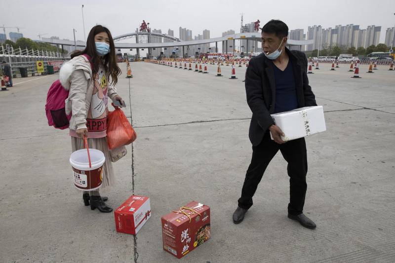 In this Thursday, April 2, 2020, photo, a man assists a woman with her belongings as they cross the expressway gate at the border of Wuhan city in central China's Hubei province. Millions of Chinese workers are streaming back to factories, shops and offices but many still face anti-coronavirus controls that add to their financial losses and aggravation. In Wuhan police require a health check and documents from employers for returning workers. (AP Photo/Ng Han Guan)