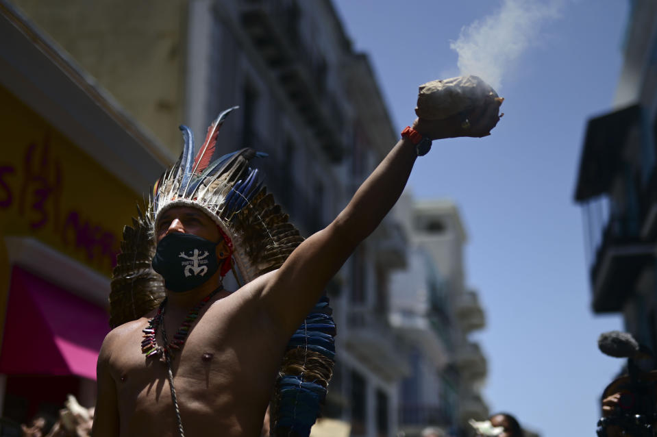 Gypsy Cordova spreads incense smoke while leading a group of activists in a march demanding statues and street names commemorating symbols of colonial oppression be removed, in San Juan, Puerto Rico, Saturday, July 11, 2020. Dozens of activists marched through the historic part of Puerto Rico's capital on Saturday to demand that the U.S. territory's government start by removing statues, including those of explorer Christopher Columbus. (AP Photo/Carlos Giusti)