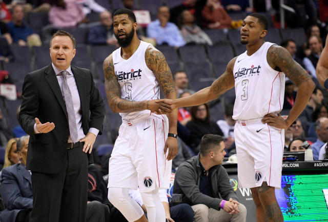 Scott Brooks (left) talks to officials following Markieff Morris' (middle) ejection Friday. (AP Photo/Nick Wass)