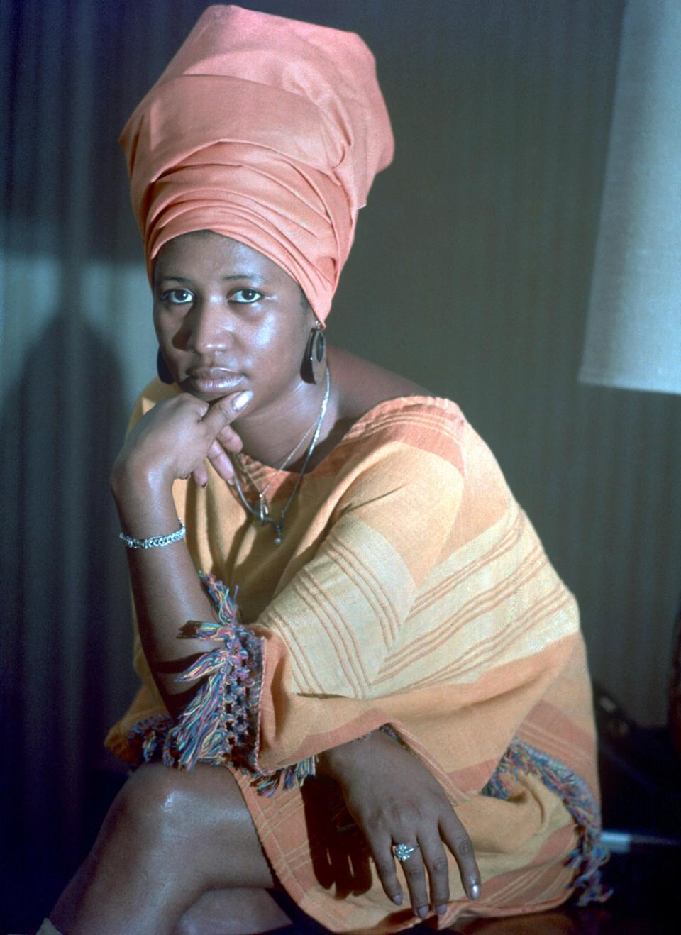 <p>Aretha Franklin poses for a portrait wearing a towering turban and colorful caftan. (Photo by Michael Ochs Archives/Getty Images) </p>