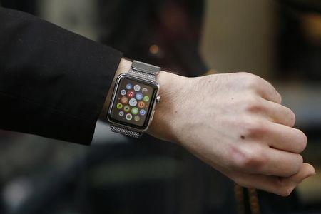 A customer presents his Apple Watch after buying it at a store in Paris