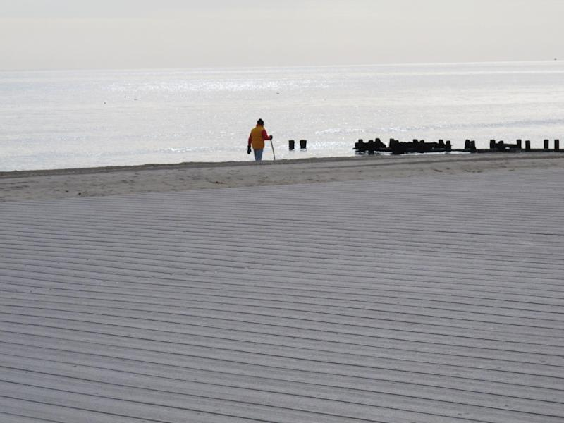 A walker strolls on the Spring Lake, N.J. beach on Monday, Jan. 21, 2013. Spring Lake is considering installing a steel sea wall between the water and the newly rebuild boardwalk, a section of which is shown in the foreground, to help protect the walkway from future storms. Spring Lake has had to rebuild its boardwalk twice from Tropical Storm Irene in 2011 and Superstorm Sandy in 2012. (AP Photo/Wayne Parry)