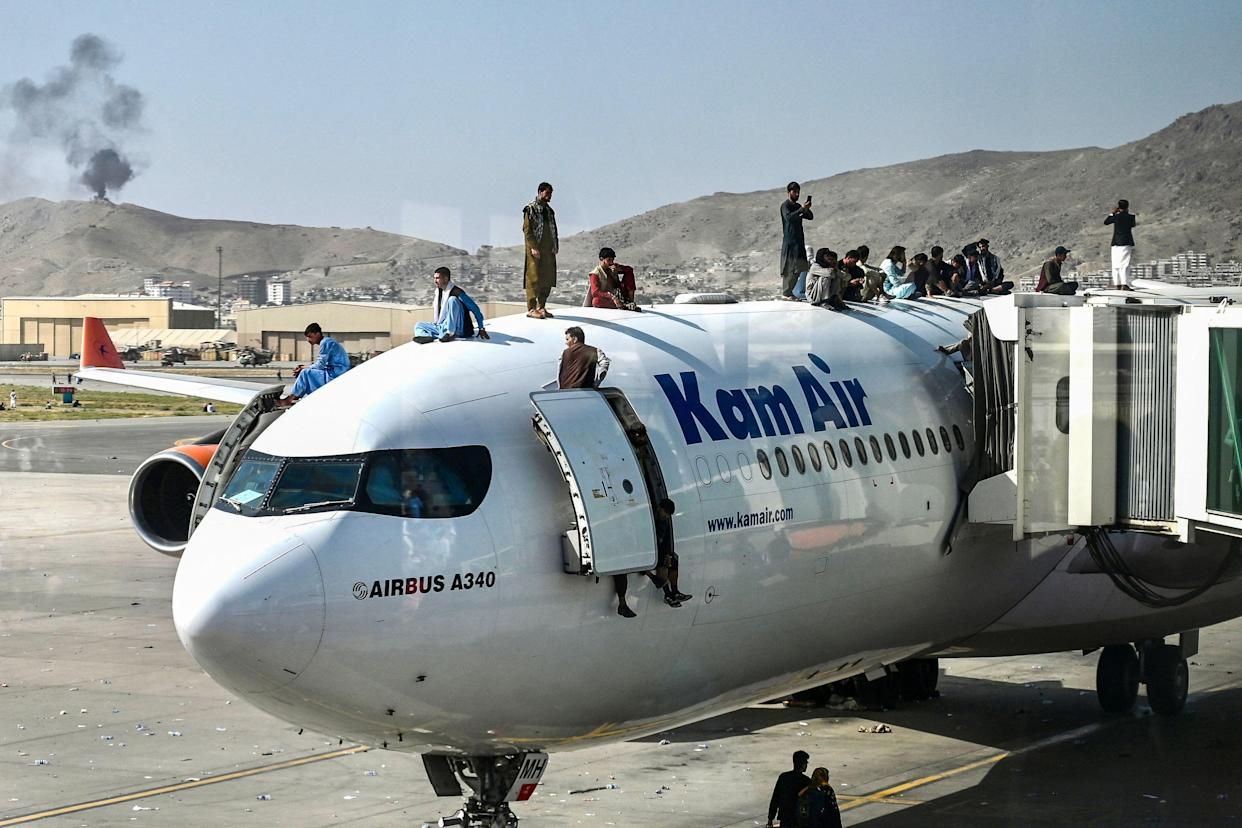Afghans climb on top of a plane at the airport in Kabul on Monday. (Photo by Wakil Kohsar/AFP via Getty Images)