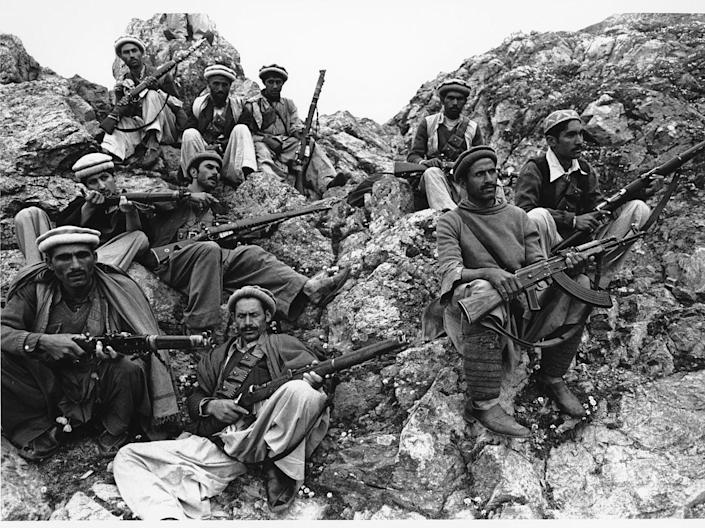 A group of mujahadeen fighters rest on a mountain.