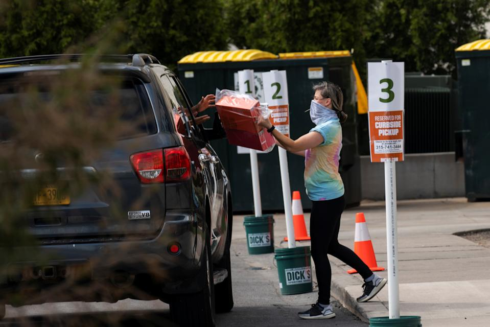 An employee of Dick's Sporting Goods in Destiny USA mall delivers products to a shopper, as customers pick up goods from retailers offering curbside pick up as the coronavirus disease (COVID-19) restrictions ease in Syracuse, New York, U.S., May 15, 2020. REUTERS/Zachary Krahmer