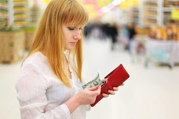 Blonde thoughtful girl gets money from her red purse in large store; shallow depth of field; Shutterstock ID 102121636; PO: DF-M