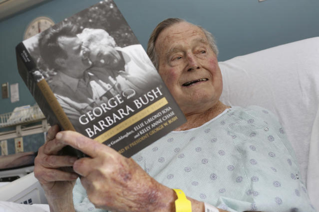 A photo of former President George H.W. Bush that was tweeted on Friday, June 1, 2018, from his hospital bed while reading a book about himself and his late wife in Biddeford, Maine. Bush is celebrating his 94th birthday in Maine. He is relaxing at his home in Kennebunkport on Tuesday, June 12, eight days after being released from the hospital where he was treated for low blood pressure. (Paul Morse/Office of George H. W. Bush via AP, File)