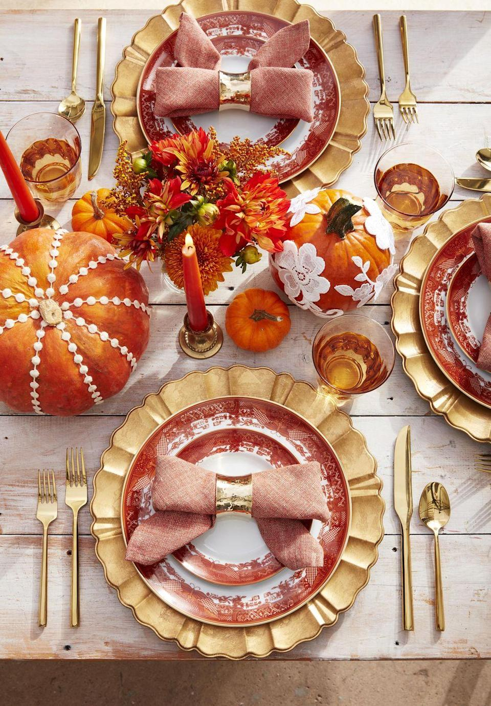 <p>Not just for wedding dresses! Hot glue lace and sewing trim on orange pumpkins and sprinkle them down the center of the table. Orange flower and bittersweet add a soft touch. Bonus: Form napkins into a bow shape and slip a gold napkin ring over the center. </p>