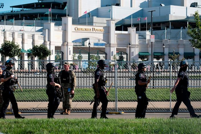Members of the Louisville Metro Police Department and Kentucky National Guard march in front of Churchill Downs during a protest against the death of Breonna Taylor on Kentucky Derby weekend in Louisville, Kentucky on September 5, 2020 (AFP via Getty Images)