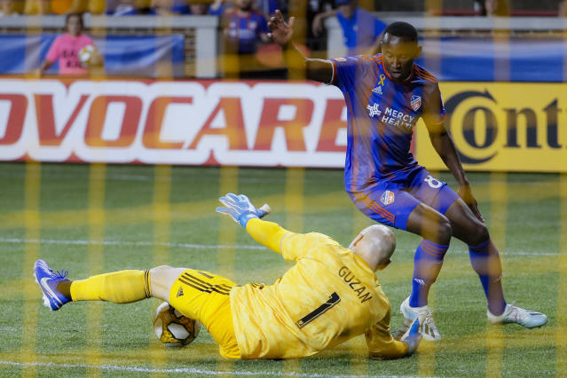 Atlanta United goalkeeper Brad Guzan (1) blocks a shot by FC Cincinnati forward Rashawn Dally (81) in the second half of an MLS soccer match, Wednesday, Sept. 18, 2019, in Cincinnati. (AP Photo/John Minchillo)