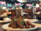 """<p><strong>Where to Get It: </strong>Morimoto Asia at Disney Springs ($14 as an appetizer, $27 as an entrée) <strong>Lou's Review: </strong>""""If you think you wouldn't order these because they're just like what you'd get from your local Chinese take-out place…think again! Iron Chef Masaharu Morimoto teamed up with the Patina Restaurant Group to bring one of his hot spots to Disney World, and in the process has created an absolute must-try menu item. These tender, meaty pork ribs are quick-fried to perfection with a slight crisp on the outside, then sprinkled with cilantro and covered with a hoisin sweet chili glaze that you'll want to bathe in. The meat literally falls off the bone, and you'll find yourself licking your fingers clean.""""</p>"""