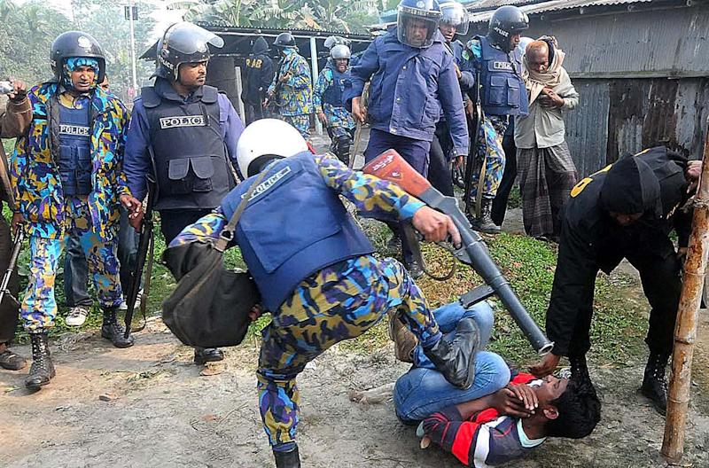 Bangladeshi policemen kick a suspect, following an attack on a polling station, in Bogra, north of Dhaka, Bangladesh, Sunday, Jan. 5, 2014. Police in Bangladesh fired at protesters and more than 100 polling stations were torched in Sunday's general elections marred by violence and a boycott by the opposition, which dismissed the polls as a farce. (AP Photo)