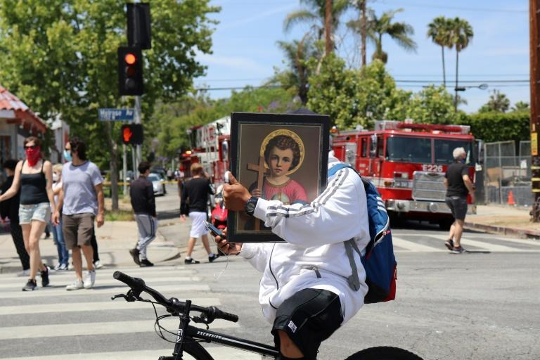 A man rides his bike carrying a religious poster as people armed with gloves and brooms get together to clean the Melrose neighborhood of Los Angeles