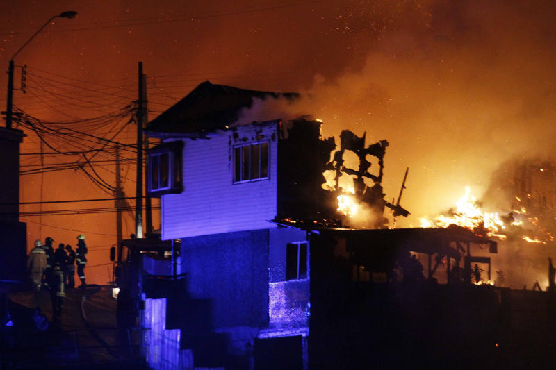 A group of firefighters stand next to burning homes as a forest fire rages towards urban areas in the city of Valparaiso, Chile, Sunday April 13, 2014. Authorities say the first fire has destroyed at least 150 homes and is forcing evacuations.( AP Photo/ Luis Hidalgo