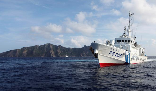 A Japan Coast Guard vessel sails in front of one of the disputed islands, named Senkaku in Japan and Diaoyu in China. Photo: Reuters