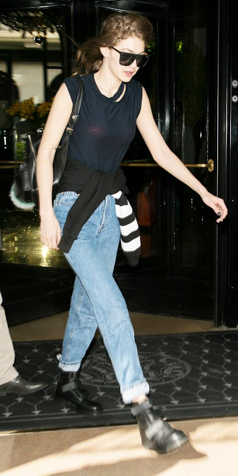 """<p>Hadid went casual while out in Paris in a ripped T-shirt (shop a similar style <a rel=""""nofollow"""" href=""""http://us.topshop.com/en/tsus/product/short-sleeve-choker-tee-6439218?bi=0&ps=20&Ntt=ripped%20t-shirt"""">here</a>) and high-waist jeans cuffed at the ankle to show off her black combat boots. She finished off the look with a pair of oversize black sunglasses, a leather shoulder bag, and a sweatshirt tied around her waist.</p>"""