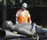 A workman looks at the statue of Harry F. Byrd, Sr., former Virginia Governor and U. S. Senator, lying on a pallett after it was removed from the pedestal in Capitol Square in Richmond, Va. Wednesday, July 7, 2021. The General Assembly approved the removal during the last session. (Bob Brown/Richmond Times-Dispatch via AP)