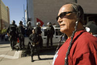 """FILE - In this Saturday, Oct. 6, 2007 file photo, American Indian Movement activist Russell Means looks at the start of the Columbus Day Parade in Denver, Colo. Columbus Day became a national holiday in 1968, endorsed by Congress and President Lyndon Johnson as a tribute to immigrants and as a """"declaration of willingness to face with confidence the imponderables of unknown tomorrows,"""" according to a Senate report at the time. But over the past 40 years, as Columbus' image has shifted from the """"discoverer of America"""" to that of a racist and imperialist, some cities and states have either changed the holiday's name or used the day to honor others. (AP Photo/Peter M. Fredin, File)"""