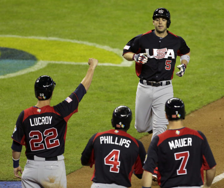 United States's David Wright is greeted by teammates after hitting a grand slam in the fifth inning of a World Baseball Classic game against Italy Saturday, March 9, 2013, in Phoenix. (AP Photo/Charlie Riedel)