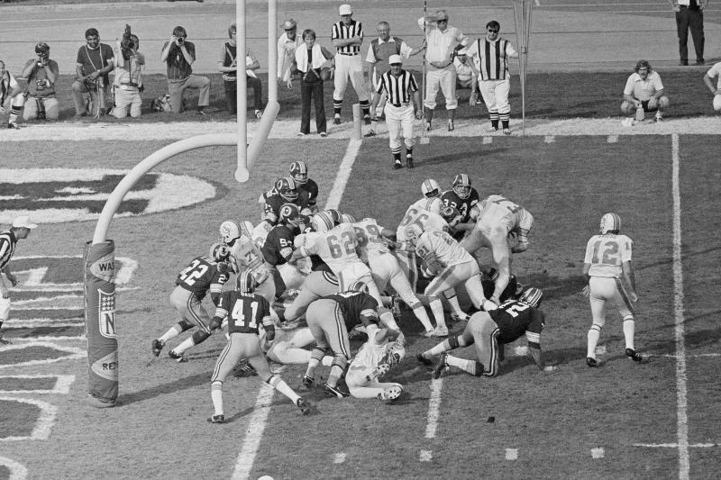 FILE - In this Jan. 14, 1973 file photo, Miami Dolphins' Jim Kiick (21) follows teammates Jim Langer (62) and Larry Csonka (39) to score against the Washington Redskins during Super Bowl VII in Los Angeles. The perfection of the 1972 Miami Dolphins has earned them the nod as the NFLs greatest team. The 1972 Dolphins edged the 1985 Chicago Bears for the NFLs greatest team in balloting by 59 national media members as part of the NFLs celebration of its 100th season. (AP Photo)