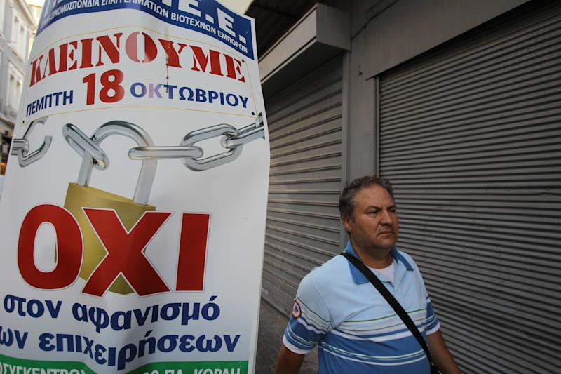 "A pedestrian passes closed shops and a poster that reads: ""We Close, Thursday 18 October. No to the extinction of our businesses"", as shopkeepers shut down for the 24-hour nationwide general strike on Thursday, Oct. 18, 2012. Labor unions in recession-hobbled Greece are holding another general strike against a new harsh austerity program, as European leaders beset by a deep debt crisis and economic stagnation gather for a summit meeting in Brussels. (AP Photo/Thanassis Stavrakis)"