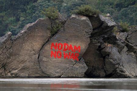 A graffiti is seen on a stone at the confluence of the Mali and Nmai river at Myitsone, outside Myitkyina, capital city of Kachin state, Myanmar