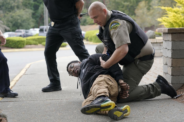 Kevin Burton-Crow, right, of the Thurston Co. Sheriff's Dept., handcuffs Naseem Coaxum, an actor playing the role of a person causing a disturbance at a convenience store, during a training class at the Washington state Criminal Justice Training Commission, Wednesday, July 14, 2021, in Burien, Wash. Washington state is embarking on a massive experiment in police reform and accountability following the racial justice protests that erupted after George Floyd's murder last year, with nearly a dozen new laws that took effect Sunday, July 25, but law enforcement officials remain uncertain about what they require in how officers might respond — or not respond — to certain situations, including active crime scenes and mental health crises. (AP Photo/Ted S. Warren)